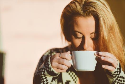 Une femme boit dans une tasse blanche une boisson chaude pouvant être du café ou du thé