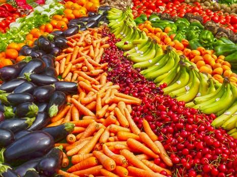 Il y a une douzaine de rangées de fruits et légumes présentés sur sur un étal. La photo est très colorée avec les différents fruits et légumes de couleurs mauve pour les aubergines, orangée pour les carottes, rouge vif pour les cerises, jaune pour les bananes, vert pour les poivrons, rouge pour les tomates. Tous ces beaux fruite et légumes nous apportent les bons minéraux dont notre corps à besoin.