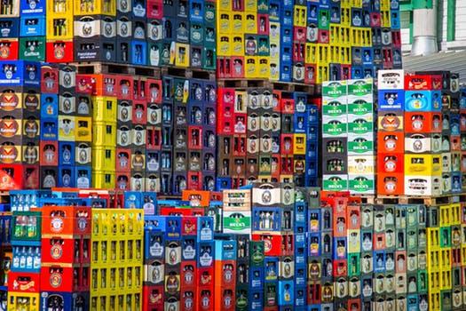 Photo d'un stock de caisses de bouteilles d'eau. Les caisses d'eau emplilées sont multicolores. Cela donne une idée des quantités innombrables de bouteilles d'eau qui circulent dans le monde