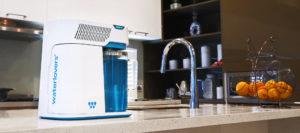Le distillateur d'eau Waterlovers est posé sur un plan de travail dans une cuisine équipée. Il s'intègre parfaitement à l'environnement d'une cuisine.